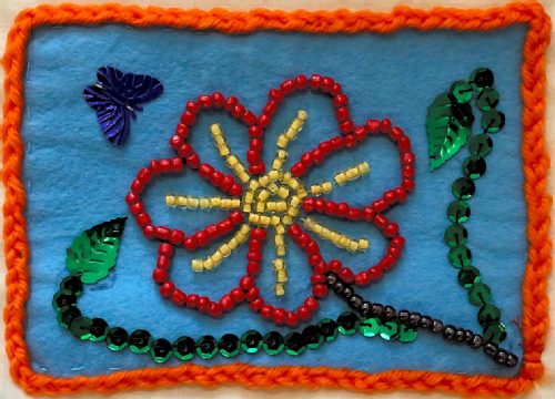 A red and yellow flower on a blue background made from small beads.