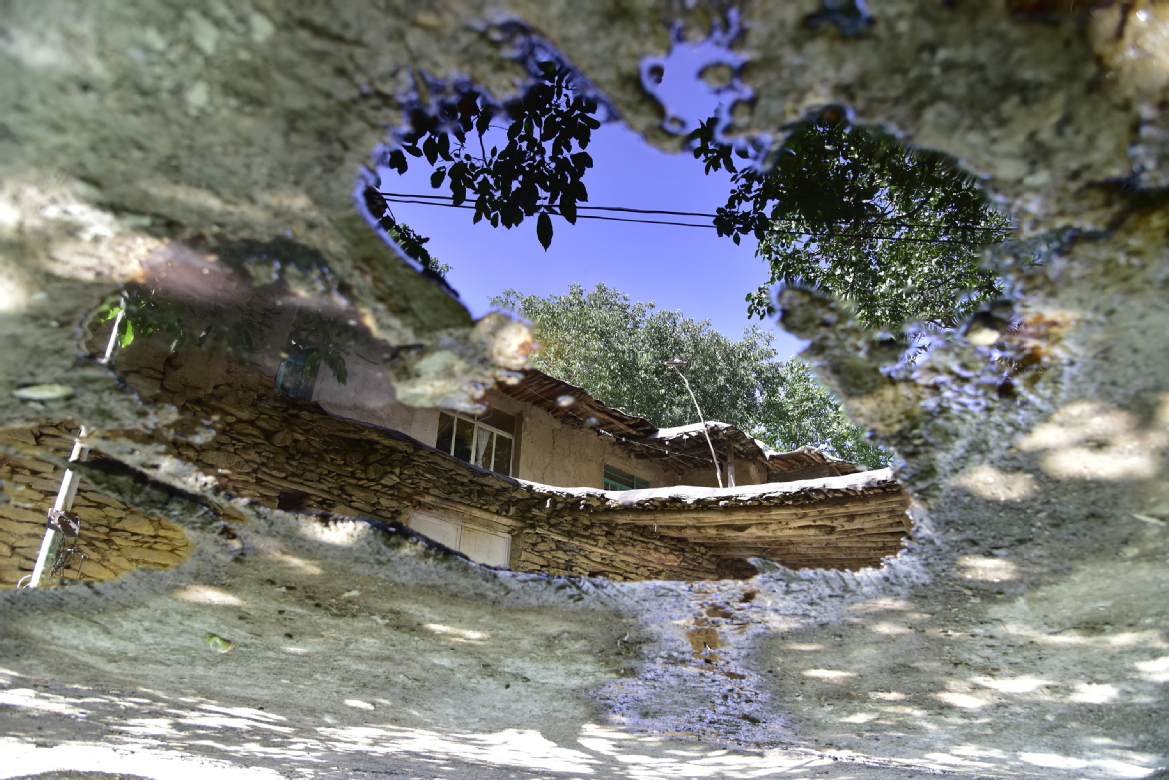 A photo of a house reflected in a pool of oil