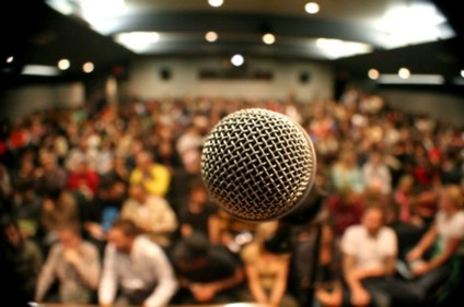 A microphone in front of a packed audience