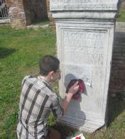 student_making_a_rubbing_of_ancient_inscription