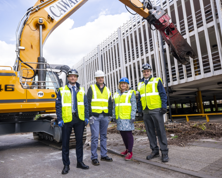 Representatives from the Faculty of Arts, Estates and the contractor Bowmer and Kirkland are standing infront of a large demolition lorry and besides the old Car Park 7.