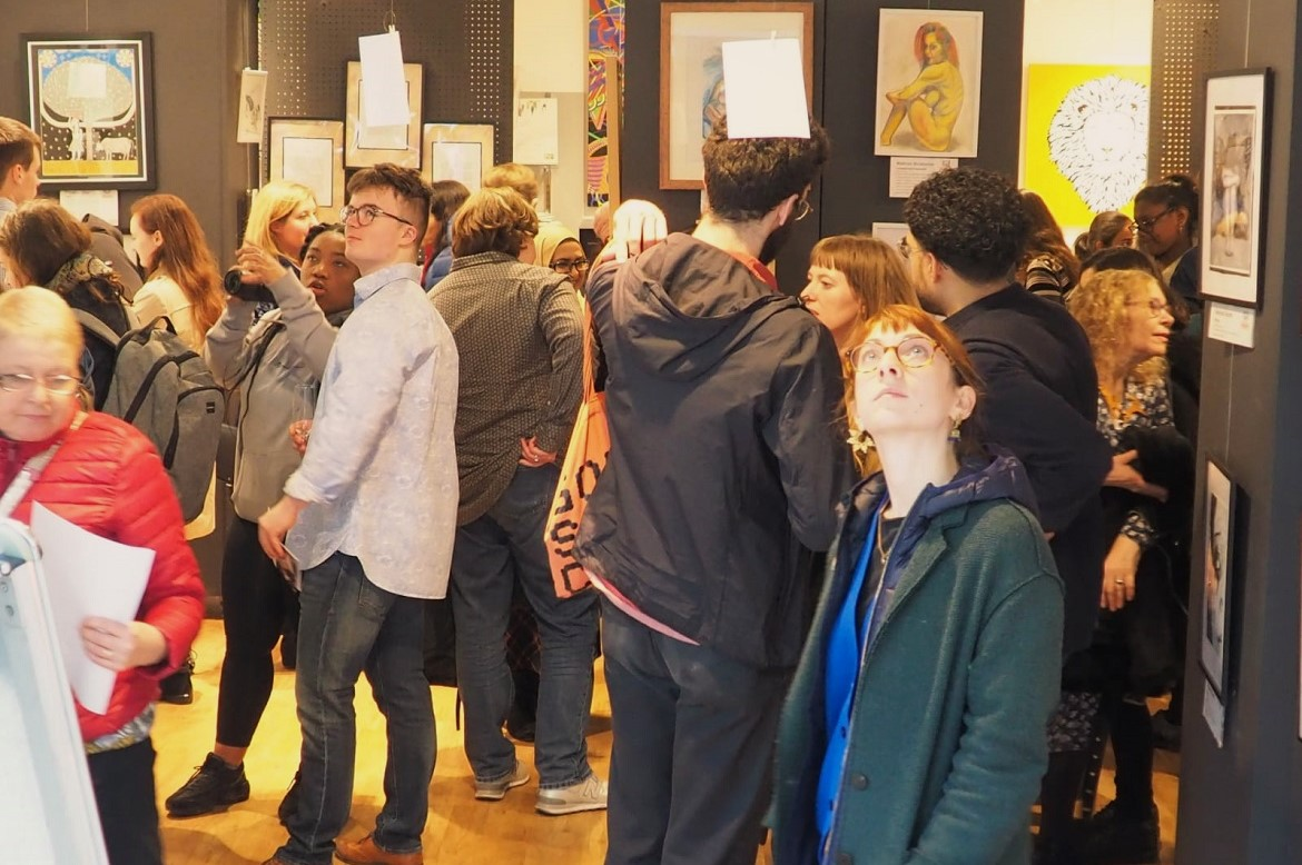 Visitors looking at the pieces of artwork at the exhibition