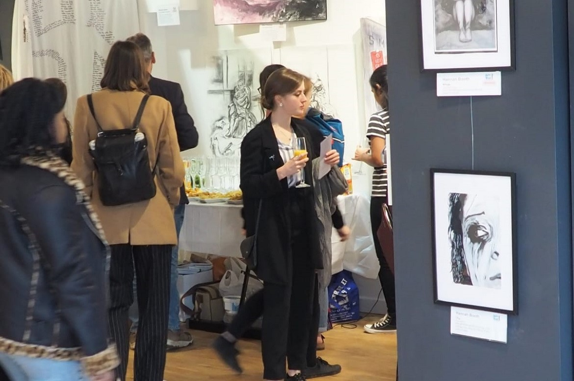 Visitors looking at pieces of art at the exhibition
