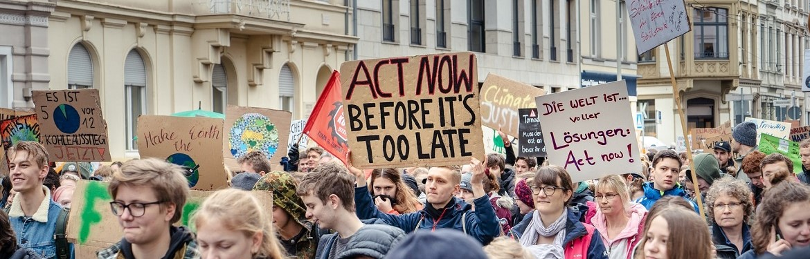 Protesters at Fridays for Future, 15.03.19, Bonn. Someone is holding a placard that reads ' Act now, before it is too late'