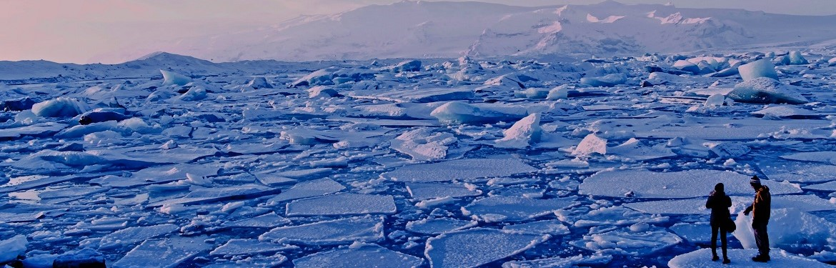 Two people watching breaking ice sheets