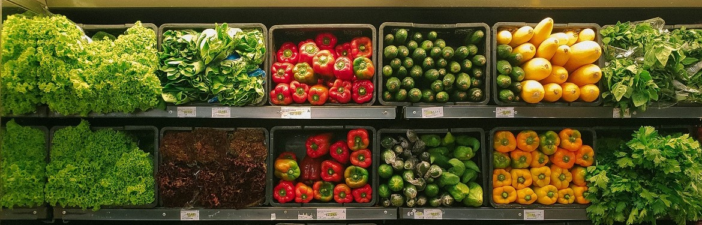 Vegetables including kale, peppers, and butternut squash lined up on supermarket shelves