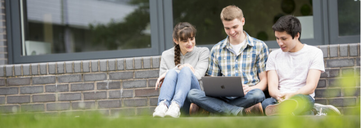 Students sat around a computer outside