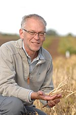 Prof Holub in a field holding navy beans