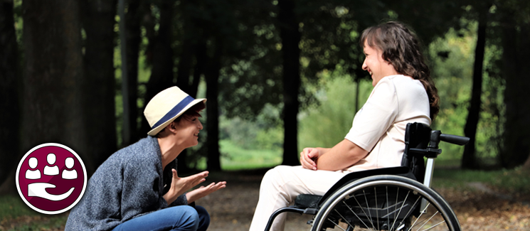 Social Care - two people talking, one in a wheelchair, one crouching down