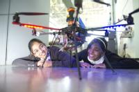 Abinaya Muraleeharan and Isha Patel, both 11, from Joseph Cash Primary School, Coventry, looking at an unmanned aerial inspection vehicle created by WMG