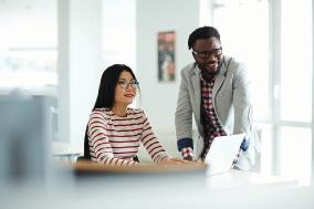 Man and a woman in professional office attire smiling near to a laptop.