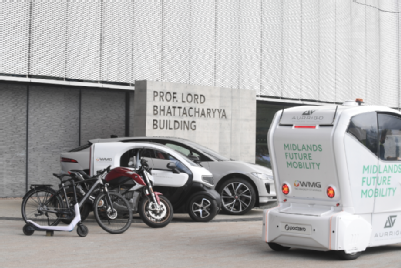 Series of micro-mobility vehicles parked outside the NAIC building. This includes six vehicles: A scooter, e-bikes, small Electric Vehicle, larger Electric Vehicle and a Midlands Future Mobility pod.