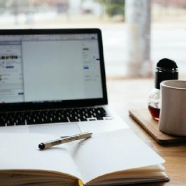 Laptop, paper and pen, coffee - The online learning environment.