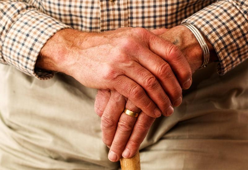 Elderly man's hands on walking stick