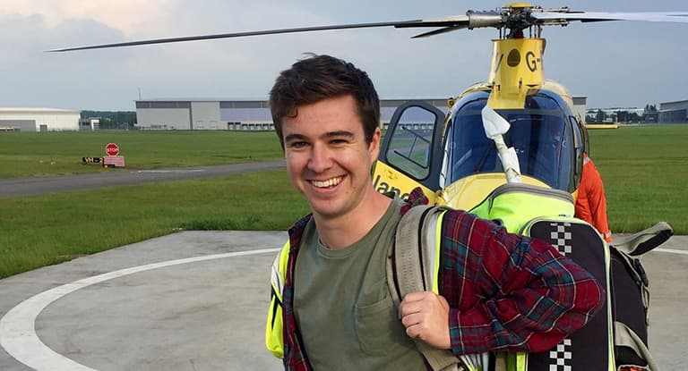 Warwick medical student stood in front of helicopter