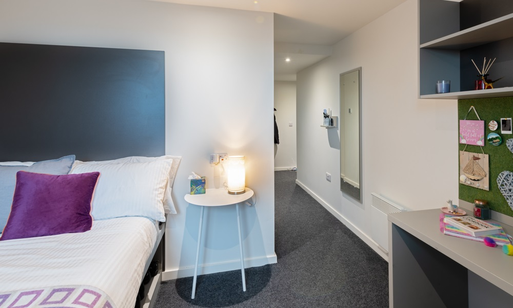 Deluxe en suite bedroom with bed, bedside table, desk, wall shelving and mirror