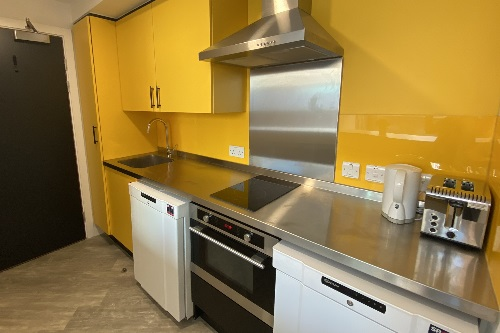 Kitchen area with oven, sink, fridge, cupboard space and work surface