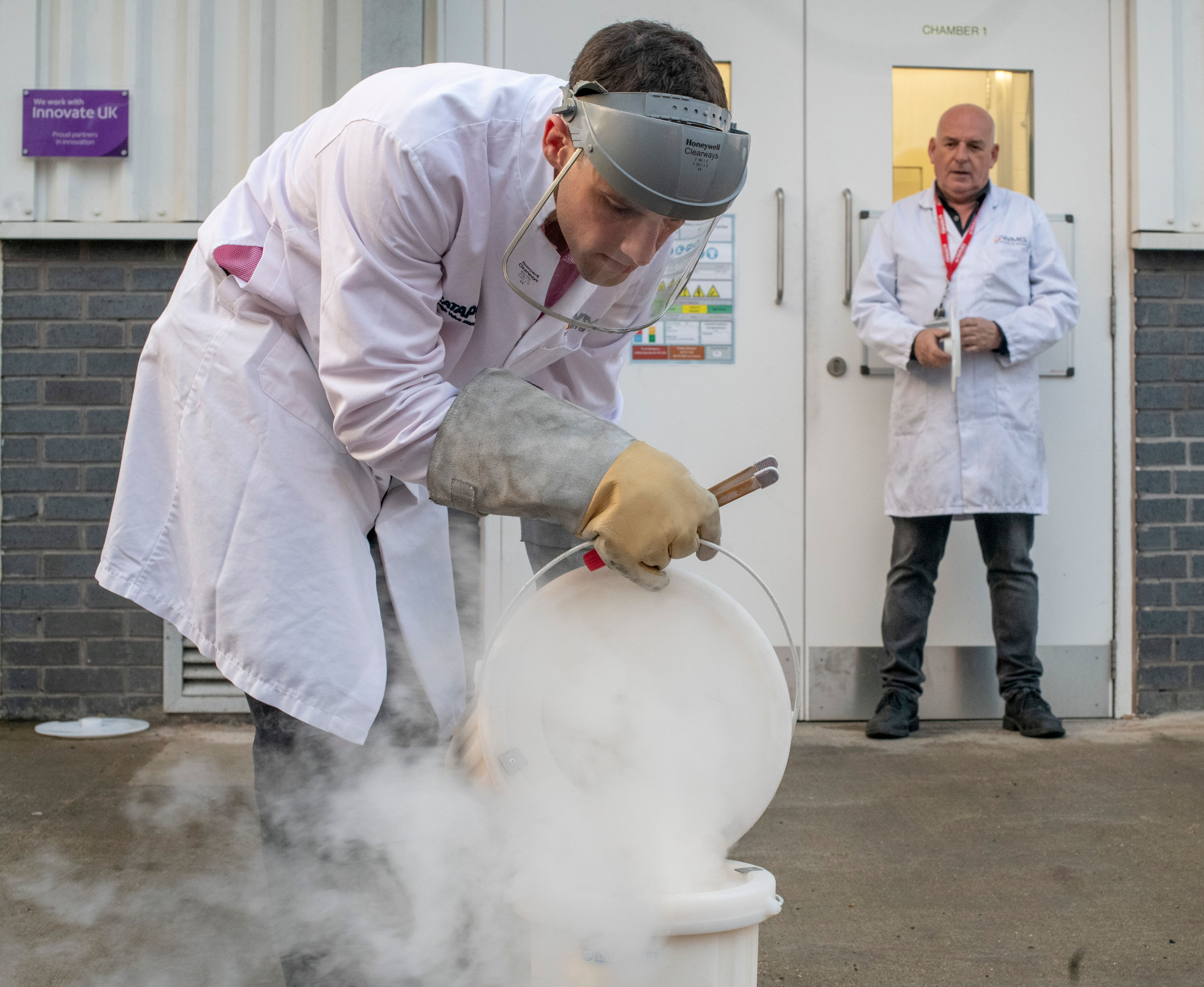 Grandjean wears a white lab coat and a safety mask as he looks down into a container with white gas rising out of it containing the battery
