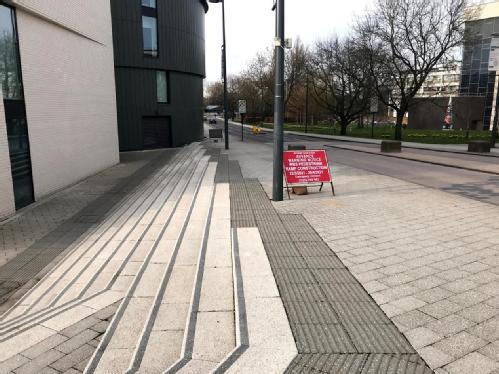 existing tapered stairs with tactile paving and red signs showing location