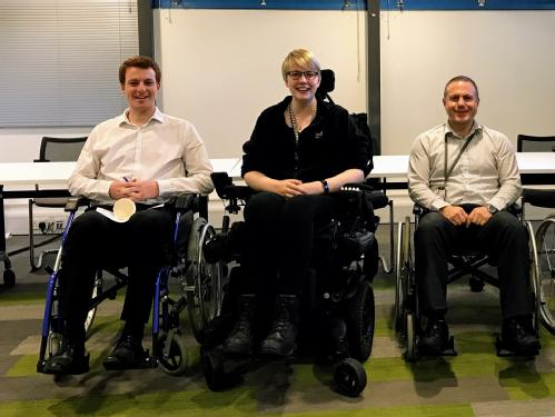 A picture of two happy participants of the Wheelchair Challenge sitting in manual wheelchairs and Accessibility Officer, Jenny Wheeler In the middle.
