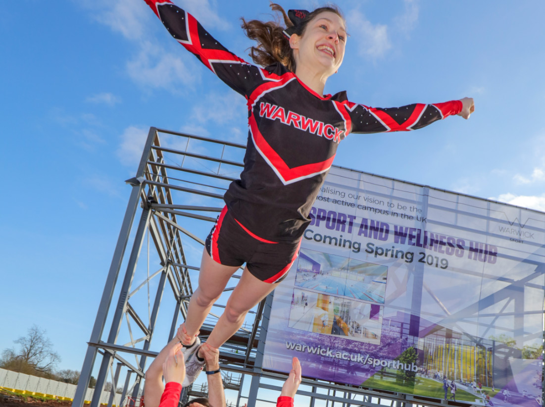 A cheerleader posing in front of the Sport and Wellness Hub banner