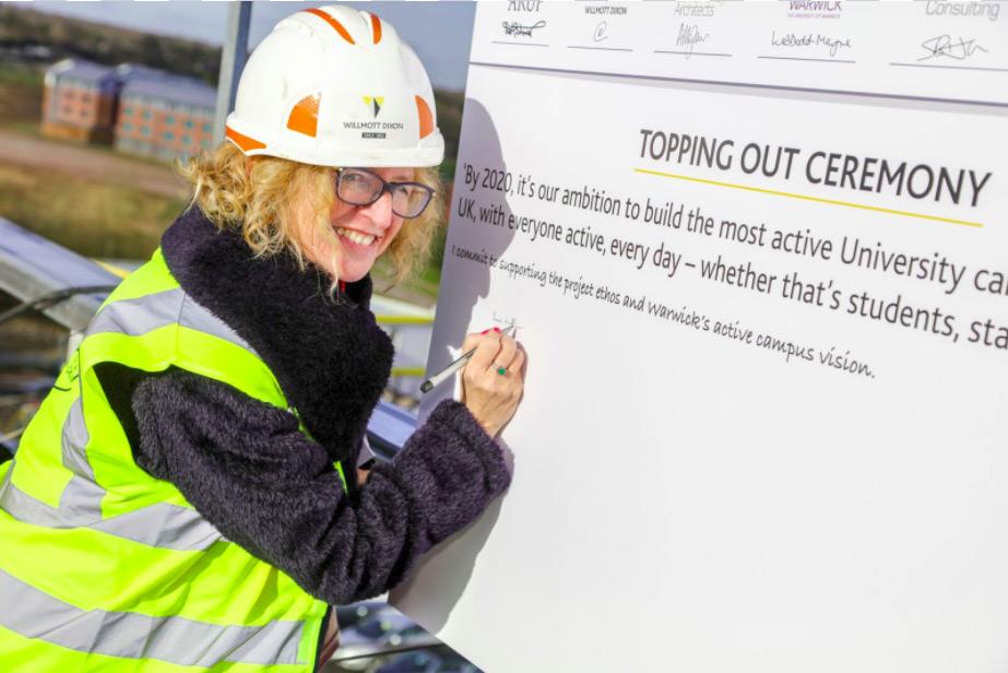 Registrar Rachel Sandby-Thomas signing the board at the Sport and Wellness Hub site