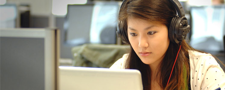 A female student wearing head phones and working on a laptop in the Library