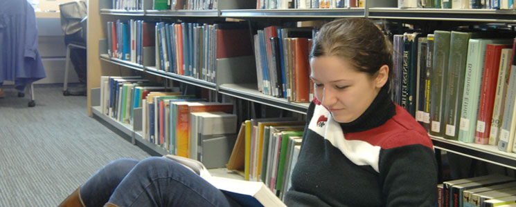 School/college student reading in amongst the bookshelves in the Library