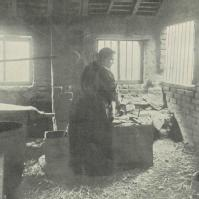 Woman chainmaker (and child) at Cradley Heath, c.1906