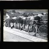 A line of cyclists bent over bridge, watching a race