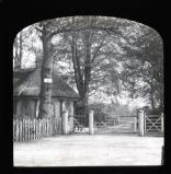 White gate and house with old trees