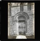 Ornate sculpted door frame around iron braced door