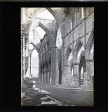 Ruins of cathedral or abbey, arches still standing but no roof. Looking towards large window.