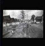 Log bridge and woman washing in town