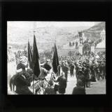 The flag preceded by a British band leaving the city on the pilgrimage to Neby Mousa the reputed tomb of Moses in the Wilderness