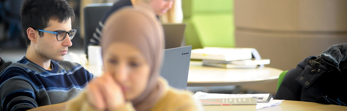 Male student using laptop in Research Exchange with female student in foreground