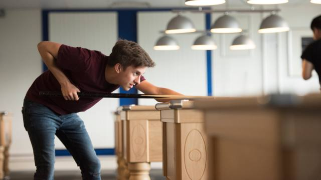 A student lines up his shot at a pool table in our student's union.
