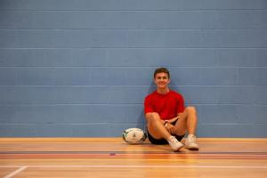student_sitting_with_rugby_ball_in_sports_centre.jpg