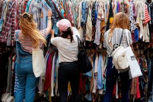 three_students_browsing_clothes_at_a_vintage_fair_on_campus.jpg