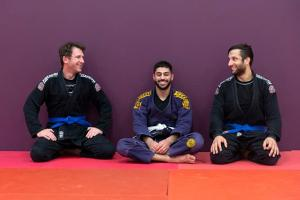 three_students_sitting_in_martial_arts_clothing.jpg