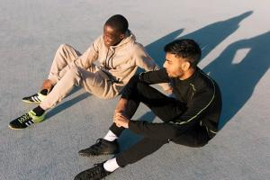 two_students_sitting_on_sports_track_with_shadow.jpg