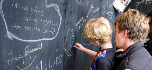 Child drawing on blackboard at an event